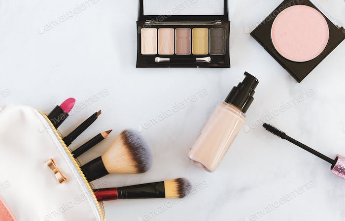 Overhead flat lay of various makeup cosmetics in neutral tones