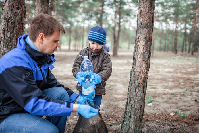Kids with their father cleaning area in forest near beach