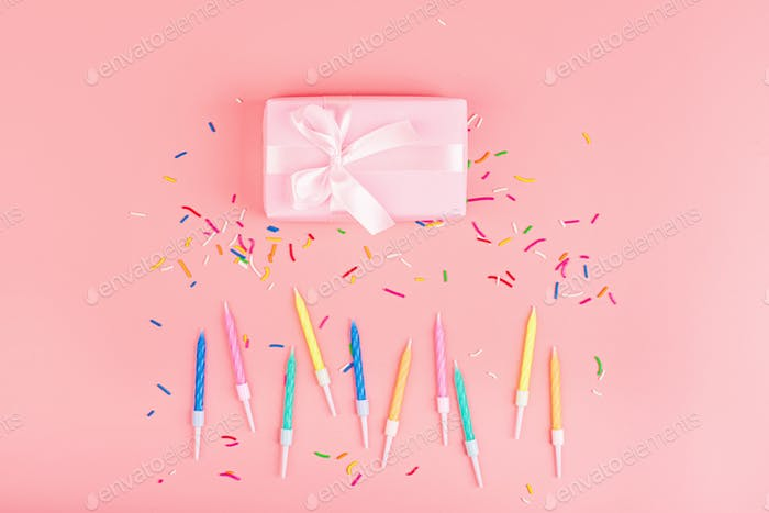 Happy birthday flatlay: gift box and candles on pink background