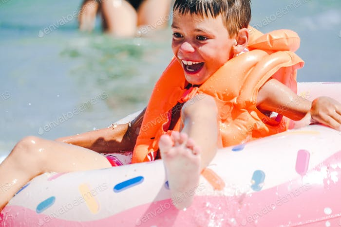 Smiling happy boy in orange inflatable vest in the sea