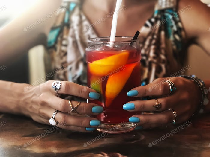 Woman in bright summer dress with fashionable jewelry accessories and stylish blue manicure 💅 drinki