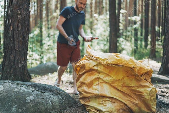 Hombre adulto voluntario limpia el bosque de basura en una bolsa grande