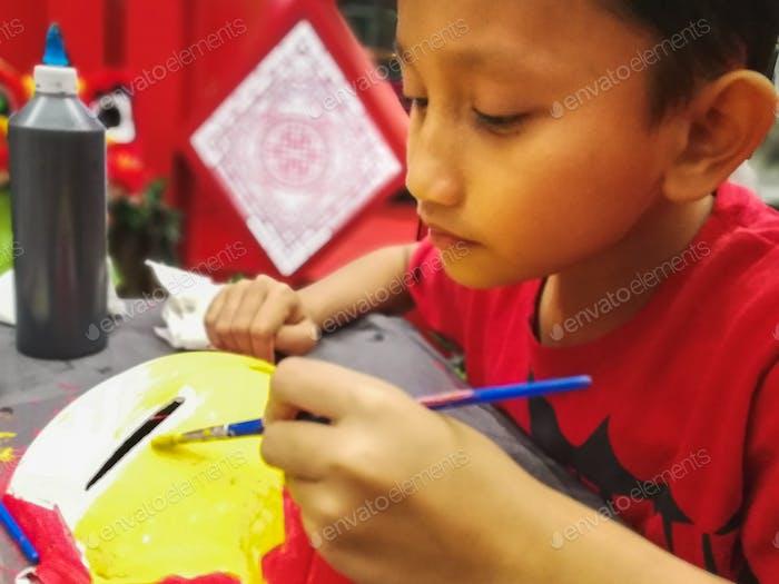 Junge malt mit Pinsel, Kunst und Handwerk.