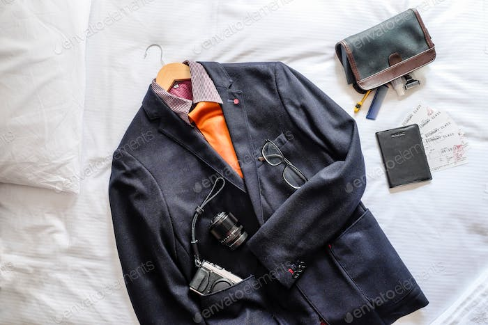 Overhead view of mens suit and travel essentials flat lay on bed