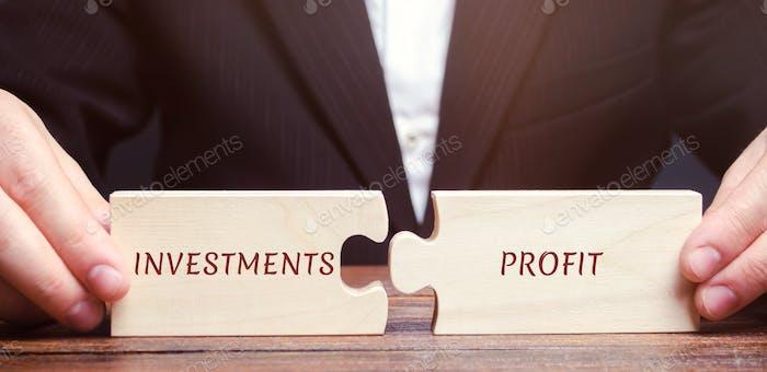 Hombre de negocios recoge rompecabezas con las palabras Inversiones y ganancias