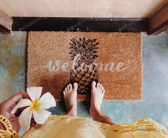 Woman standing on the door mat with a welcome writing holding frangipani flower in her hand