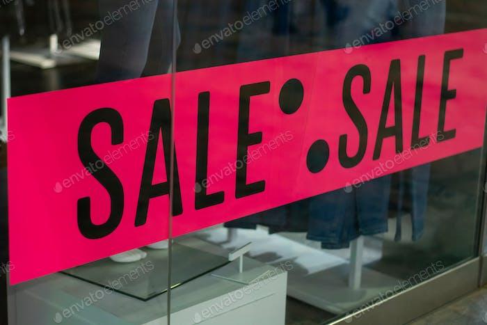 Verkauf von Werbung in einem Bekleidungsgeschäft. Leuchtend rosa Plakatschild mit dem Wort Sale am Eingang