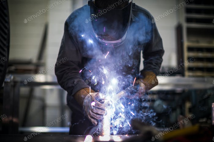 Man welds aluminum piping together