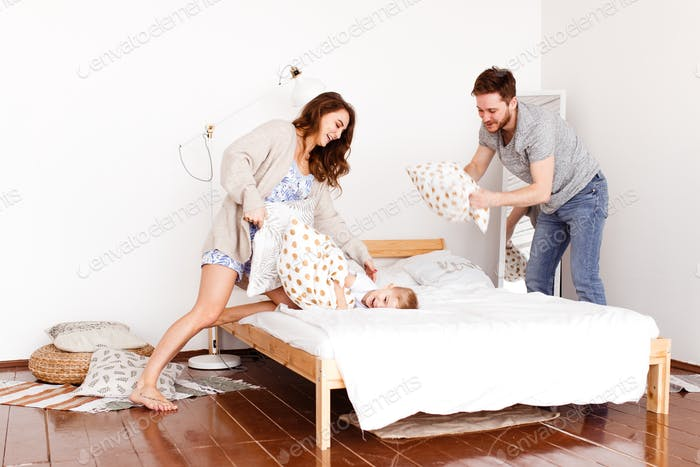 Mama, Papa und 3-jähriger Sohn kämpfen mit Kissen, lachen, täuschen, spielen und Spaß auf dem Bett haben