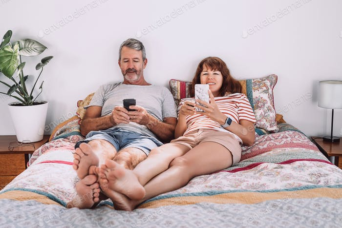 Middle-aged couple laying on the bed and texting each on their smartphone looking at the screen.