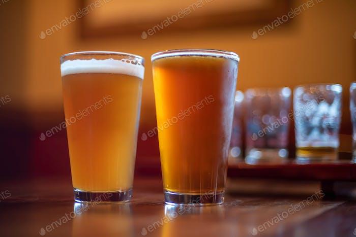 Zwei Pints Craft-Bier auf der Theke im Sonnenlicht für Produkt-Mockup oder Logo Platzierung