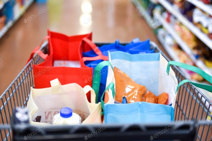 Close-up image of a shopping cart in the middle of a grocery store isle filled with reusable