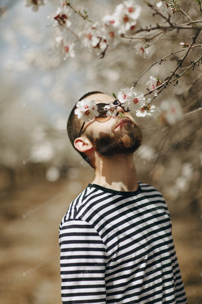 a man in a vest and glasses sniffing at the flowering tree