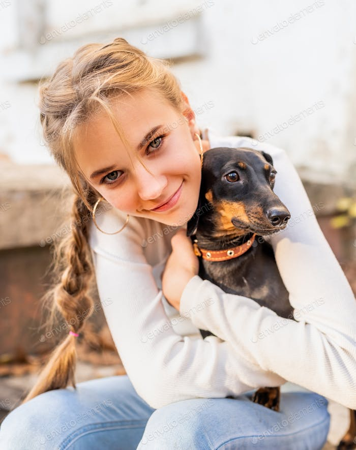 Happy teen girl hugging her dachshund dog outdoors