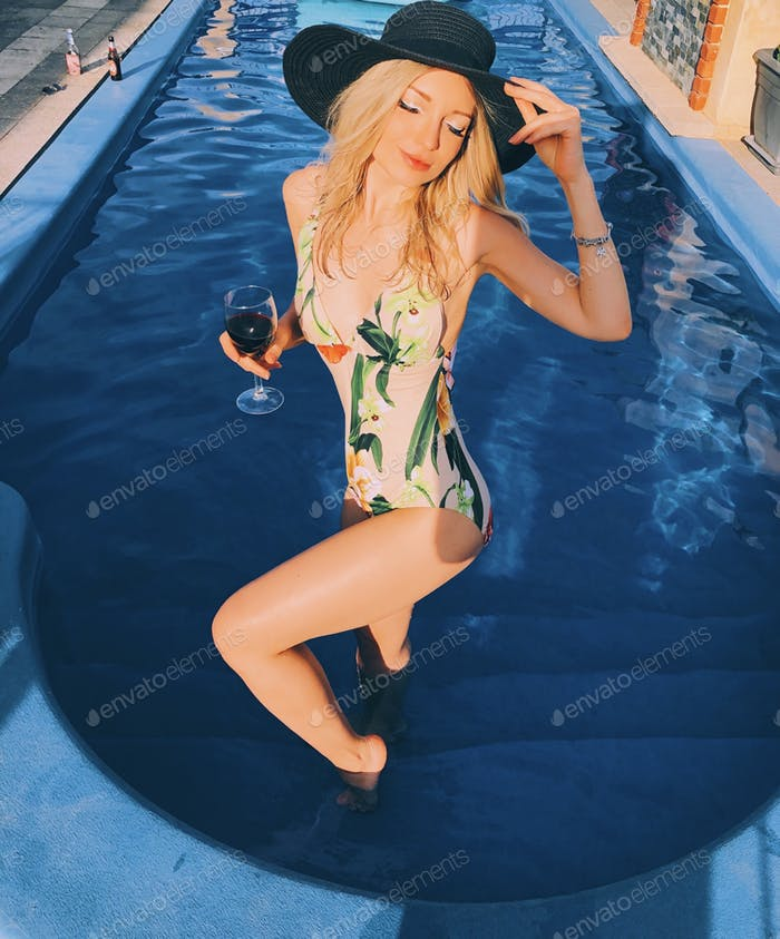 Blonde girl in a swimming pool wearing black hat and holding a glass of red wine