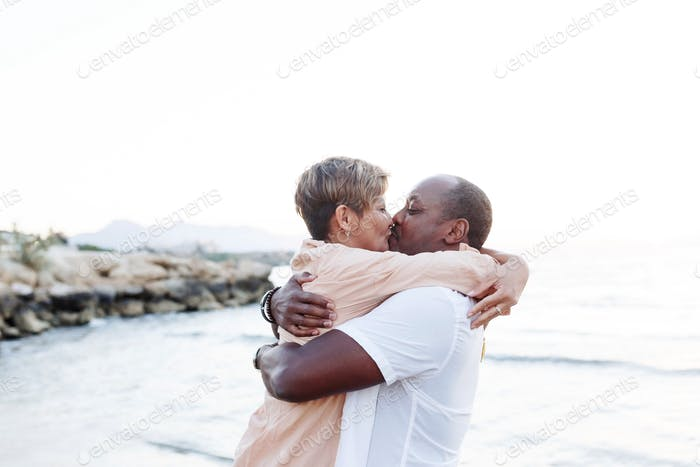 Mixed race colours of skin couple kisses