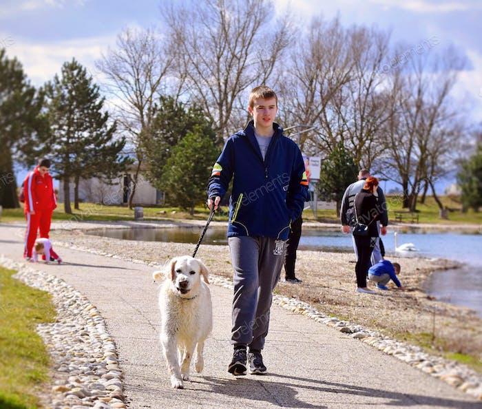 A teenage boy walking his doggie on a leash