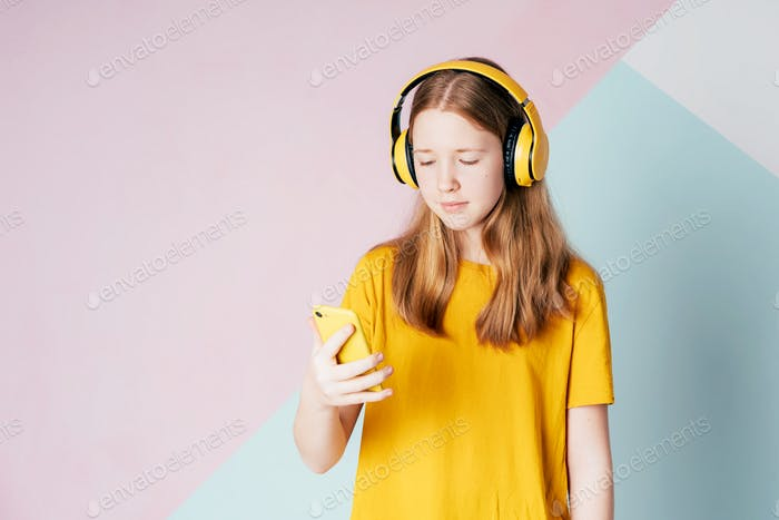 Red-haired teenage hipster girl in wireless headphones listens to a playlist on a mobile phone.