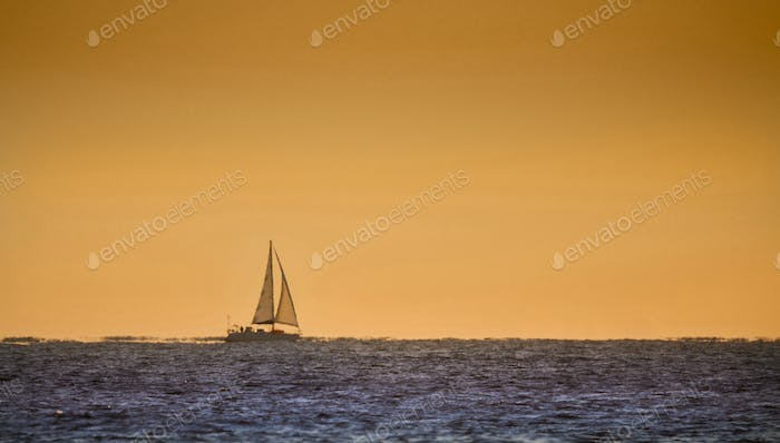 A boat on the horizon at sunrise