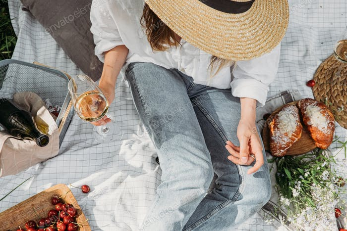 Top view of woman in straw hat sitting and having picnic. Aesthetic rustic picnic in neutral tones