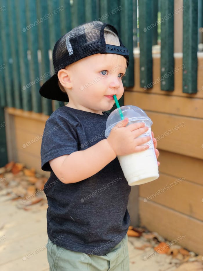 Young boy drinking a drink out of a cup while outside at a park.
