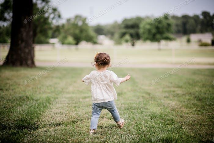 Toddler girl learning to walk in yard.