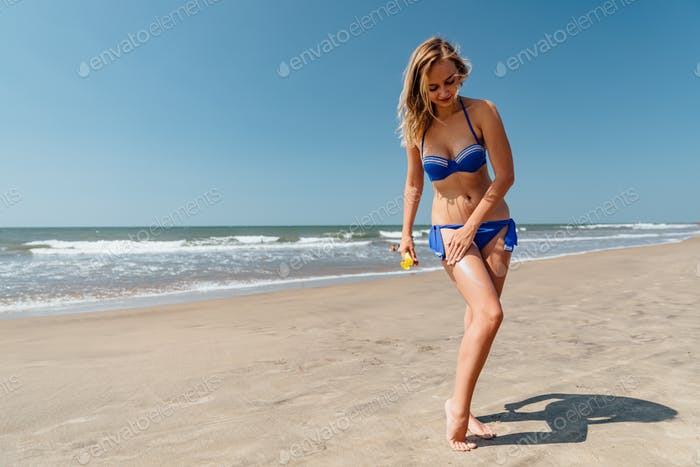 girl in a bathing suit with sunscreen