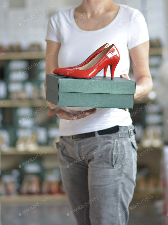 the salesman holds a box with red ladies shoes in his hand