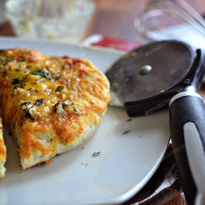 Hausgemachtes Käsebrot mit Pizzabaste, Cheddar, Koriander und Zwiebel.