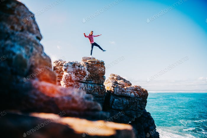 happy young man having fun balancing on cliffs above the ocean