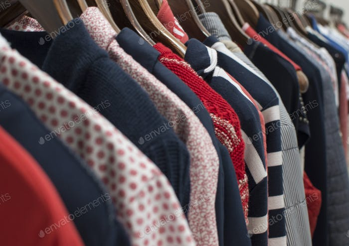 A row of red and navy clothes on a rail in a store