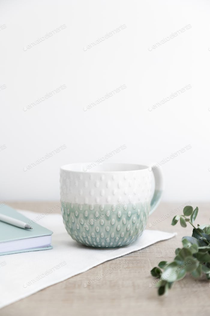 Productivity scene of coffee mug, notebook and pen