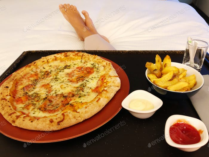 Personal perspective woman laying down in bed with the room service pizza tray