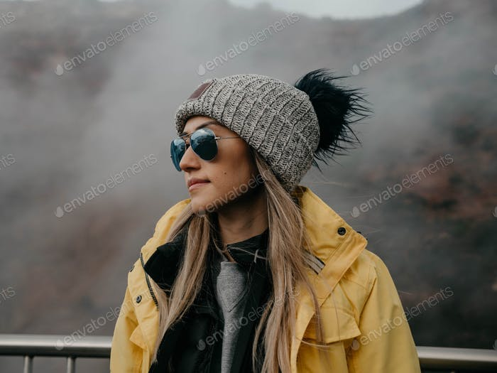 Young woman in winter fashion gear attire including jacket beanie sunglasses in foggy cold Iceland