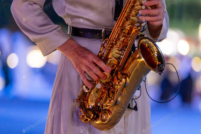 Woman playing saxophone, hands in frame