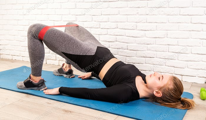 Young athletic woman doing hip bridge, working out with rubber resistance bands at home