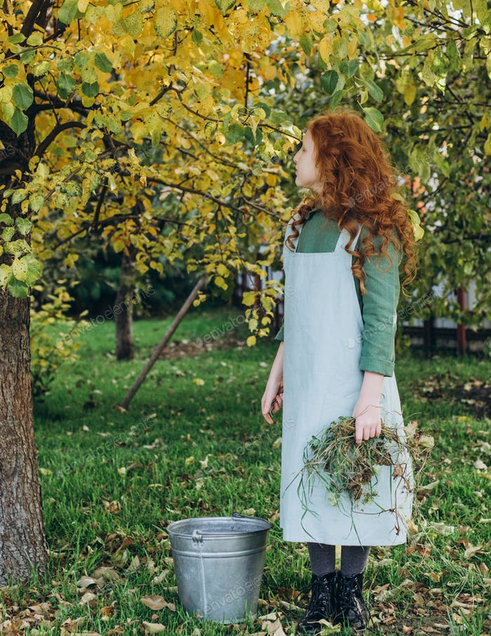 A red-haired little girl in linen clothes came to the garden to clean dry grass.