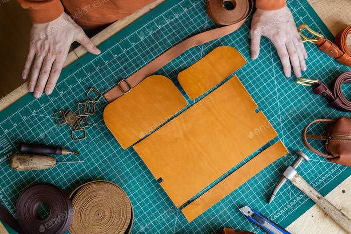Process cutting scheme of bag with equipment and materials. Male tanner working at leather workshop