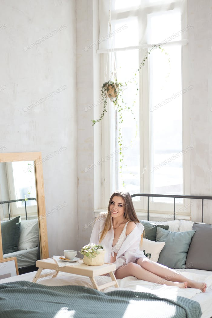 beautiful attractive happy with a delicious smile girl in a white nightgown meets the morning