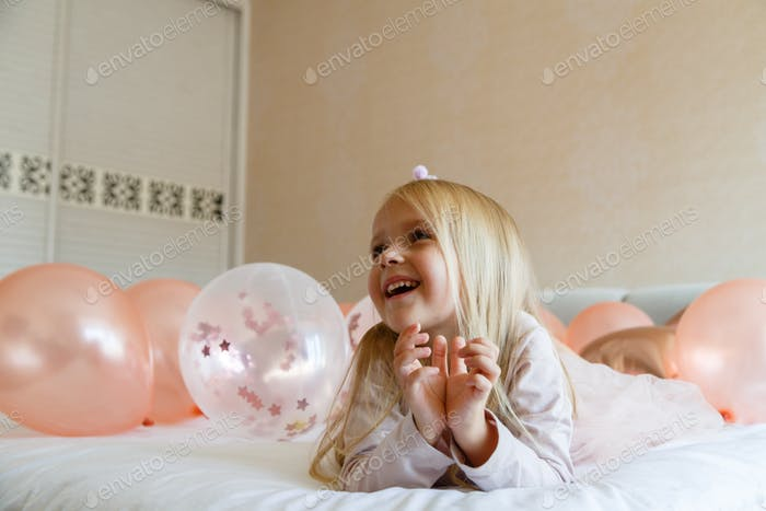 ⭐️⭐️⭐️ Nominated ⭐️⭐️⭐️    Happy little girl sitting on the bed with balloons. Birthday party