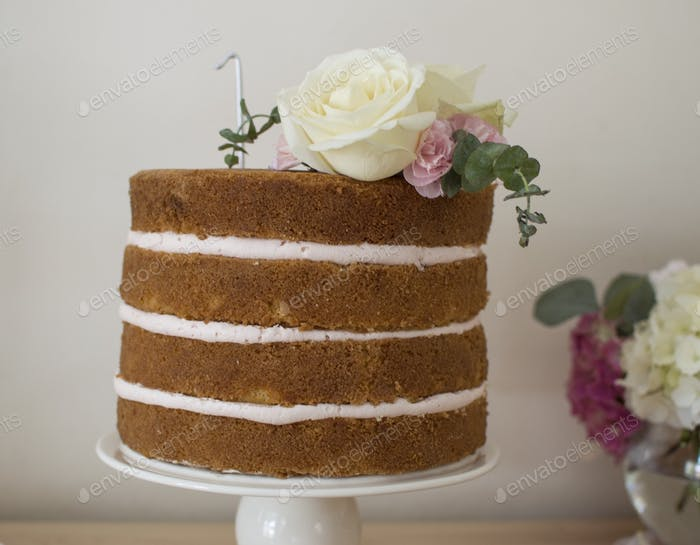 A four layer birthday cake adorned with flowers