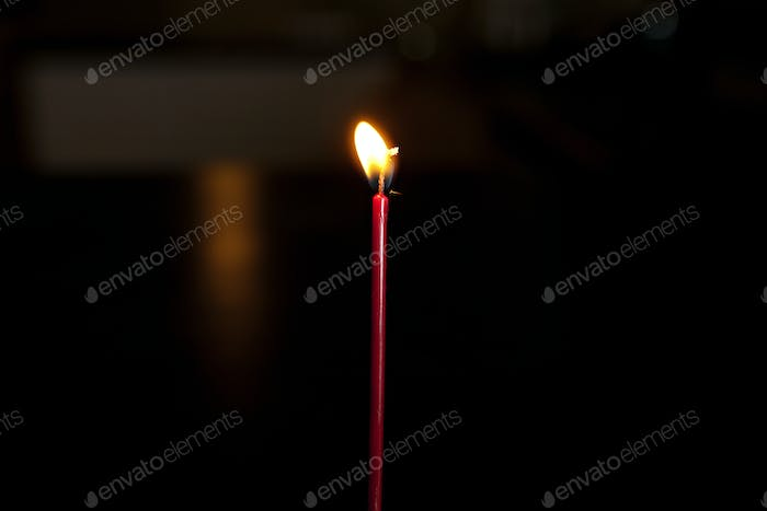 single red lit candle in the dark