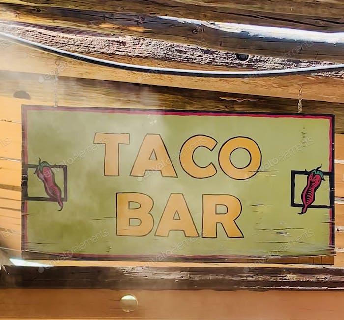 Taco-Bar-Schild mit Mistern, die ins Freie gehen auf die Terrasse eines Restaurants