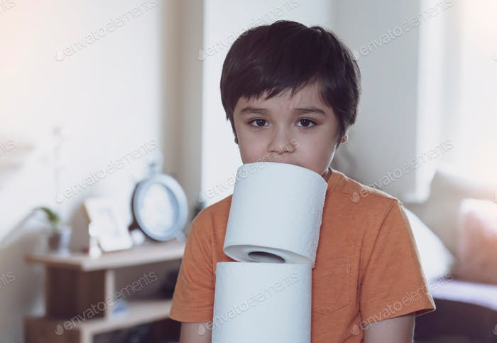 Child carrying a stack of toilet paper, Kid holding toilet roll.