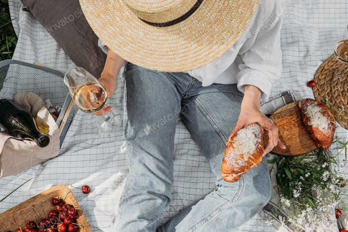 Top view of woman in straw hat sitting and having picnic with glass of white wine and croissant