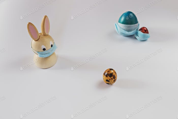 Isolated painted easter eggs in medical masks.