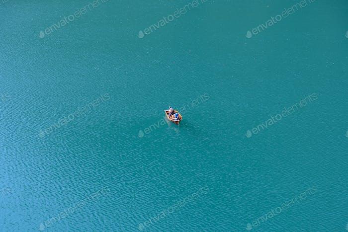Hoher Winkel, Antenne Minimalistisches Bild eines kleinen Holzbootes auf dem blauen See.