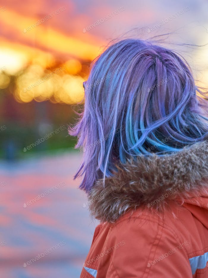 Girl with violet blue hair looking at the fiery sunset