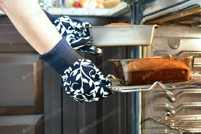 Person taking a loaves of banana quick bread out of the oven. kitchen, baking, baked goods