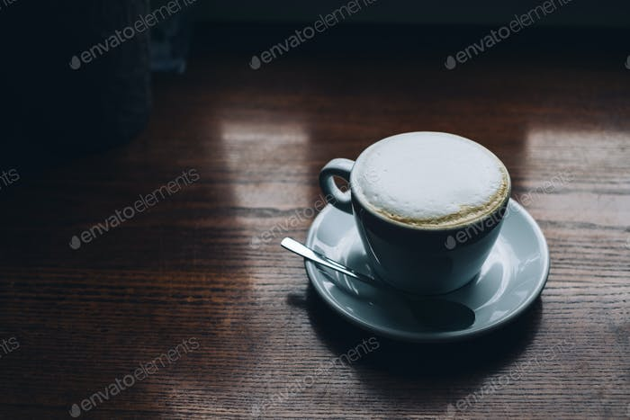 cup of cappuccino on the wooden table